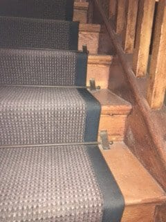 Vintage stair rods shown on wooden staircase
