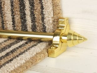 Arrow stair rod in polished brass on brown striped stair runner
