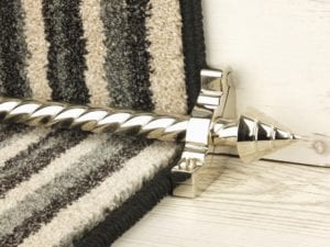 Arrow head on spiral-design stair rod in Polished Nickel, matching bracket, fitted on step with deep red stair carpet