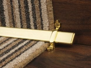 Vue stair rods in polished brass on striped carpet