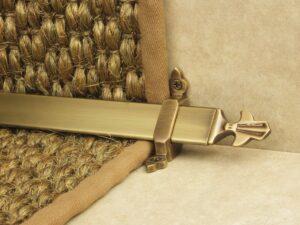 Louis design of stair rod with fleur-de-lys end, antique brass on sisal carpet