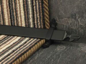 Louis design of stair rod with fleur-de-lys end, black on striped carpet