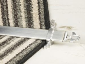 Louis design of stair rod with fleur-de-lys end, brushed chrome on striped carpet