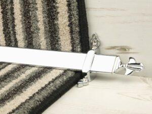 Louis design of stair rod with fleur-de-lys end, chrome on striped carpet