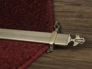 Louis design of stair rod with fleur-de-lys end, antique brass on red carpet