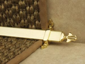 Louis design of stair rod with fleur-de-lys end, polished brass on sisal carpet