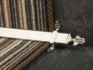 Louis design of stair rod with fleur-de-lys end, polished nickel on striped carpet