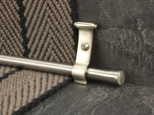 Flat stair rod in stainless steel with bracket, close-up on natural stair runner