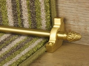 Sherbourne stair runner rod with matching bracket, satin brass on green striped stair runner