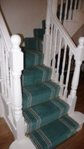 Windsor stair rods fitted on blue carpet runner, turning staircase