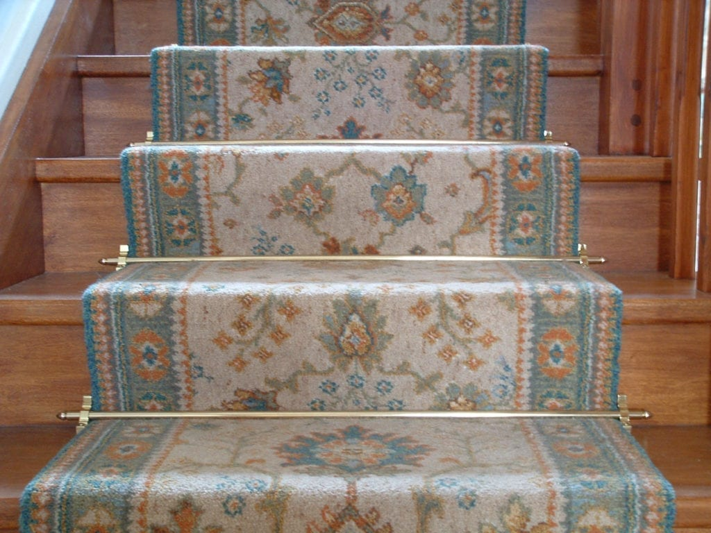 Lancaster stair rods in polished brass fitted on a patterned, blue runner