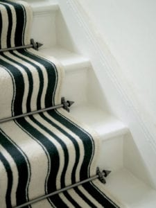 Vision Arrow stair rods in black shown on black and white striped carpet
