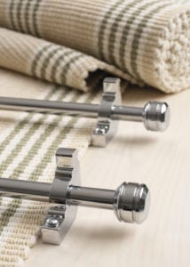 Piston stair rods polished chrome on striped, folded carpet