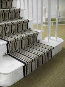 Sphere runner rod fitted on striped runner, white staircase