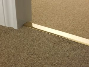 Double Z door threshold in polished brass creating smart join between tow carpets in doorway