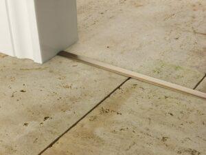 T Bar 14mm door threshold antique brass fixed between two tiled floors