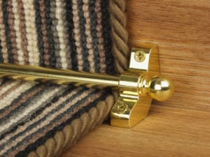 Jubilee stair rod in polished brass on striped carpet