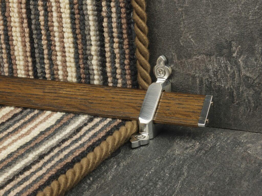 Tudor Dark wooden stair rods on striped runner carpet