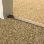 Premier Double Z9 door threshold joins two carpets in a doorway, antique brass