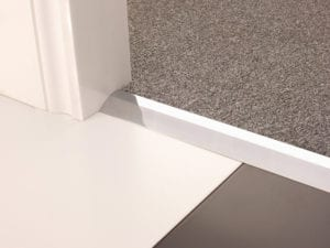 Carpet ramp joins different levels of flooring, carpet to tiles, brushed chrome
