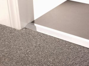 Carpet ramp joins different levels of flooring, carpet to tiles, chrome