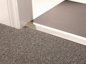 Carpet ramp joins different levels of flooring, carpet to tiles, polished nickel