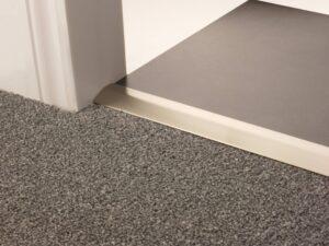 Carpet ramp joins different levels of flooring, carpet to tiles, satin nickel