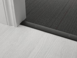 Premier Cover door plate with matching screws, connecting laminate to carpet flooring, black