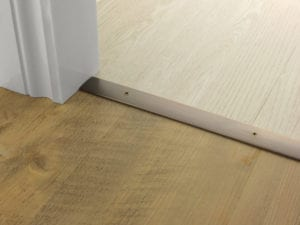 Premier Cover door plate with matching screws, connecting laminate to vinyl flooring, bronze