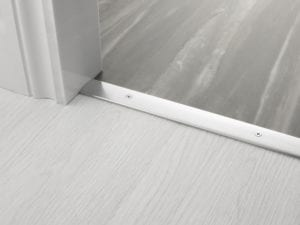 Premier Cover door plate with matching screws, connecting laminate to vinyl flooring, brushed chrome