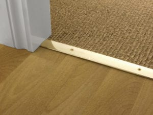 Premier Cover door plate with matching screws, connecting laminate to sisal flooring, polished brass
