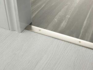Premier Cover door plate with matching screws, connecting laminate to vinyl flooring, satin nickel