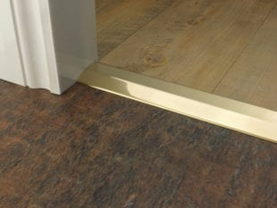 Premier 2 Way Ramp sloping door threshold, shown from laminate to vinyl, polished brass