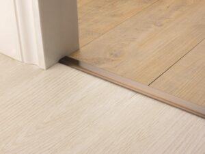 Premier Vinyl Edge floor edging, self-adhesive, shown between vinyl & timber, antique brass