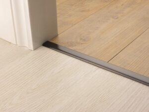 Premier Vinyl Edge floor edging, self-adhesive, shown between vinyl & timber, antique bronze