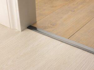 Premier Vinyl Edge floor edging, self-adhesive, shown between vinyl & timber, pewter