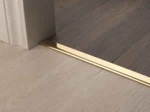 Premier Vinyl Edge floor edging, self-adhesive, shown between vinyl & timber, Polished Brass