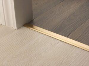 Premier Vinyl Edge floor edging, self-adhesive, shown between vinyl & timber, satin brass