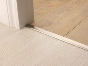 Premier Vinyl Edge floor edging, self-adhesive, shown between vinyl & timber, satin nickel