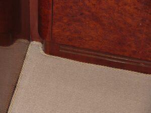 beige binding of loop pile carpet with irregular shape, shown in a luxury yacht saloon
