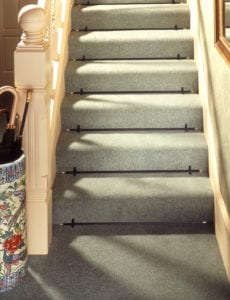 Black stair rods fitted to full width green stair carpet