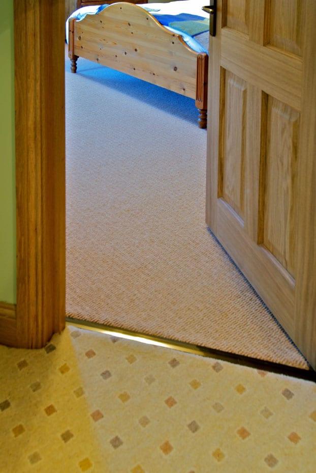 Posh door threshold joins landing to bedroom carpet in doorway, antique brass