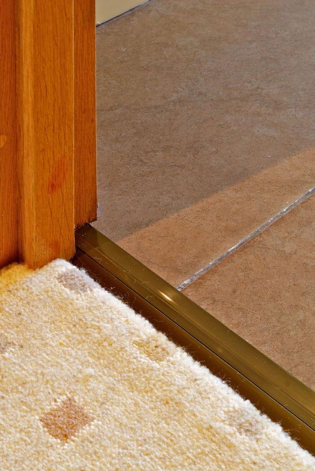 Posh door threshold carpet to tile in antique brass in doorway