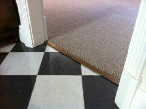 Brown floorcovering joined in doorway to black and white tiled floor with antique brass Posh door bar