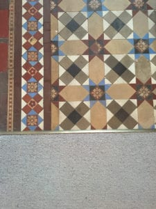 Patterned tiled floor joined to brown carpet with Premier Z door threshold, antique brass