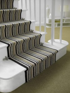 Vision Sphere runner carpet rod fitted on black and green striped stair runner, white painted staircase