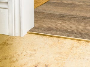 vinyl door threshold in satin brass joining LVT