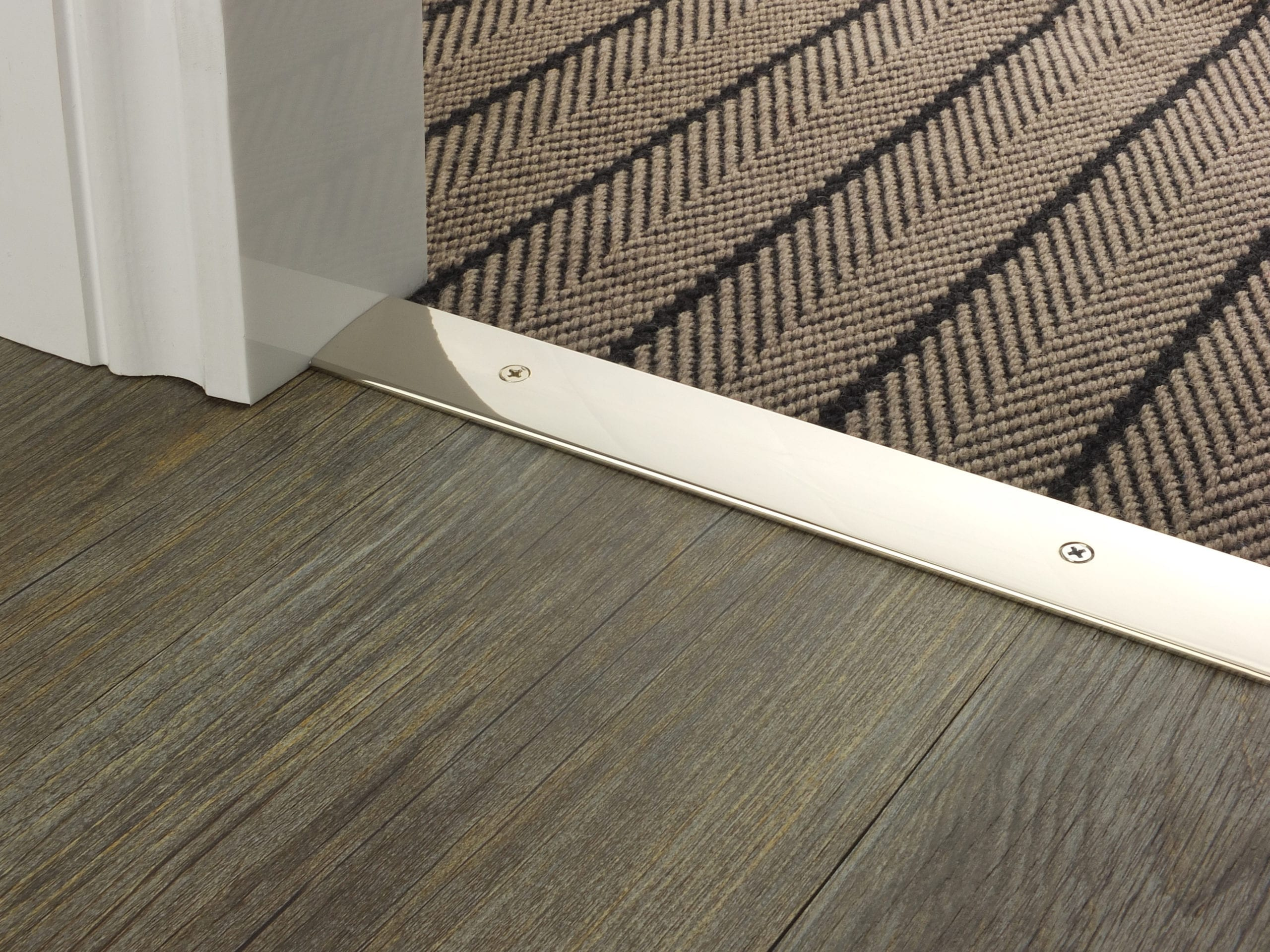 Premier Cover plate 38mm polished nickel with matching screws shown connecting a brown floorcovering to wooden floor