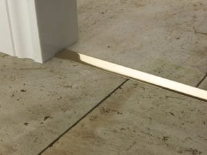 Premier T Bar self adhesive door threshold in polished brass, connecting two tiled floors