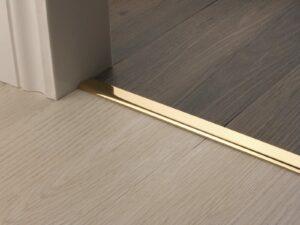 Vinyl Edge door threshold polished brass connecting vinyl flooring in doorway
